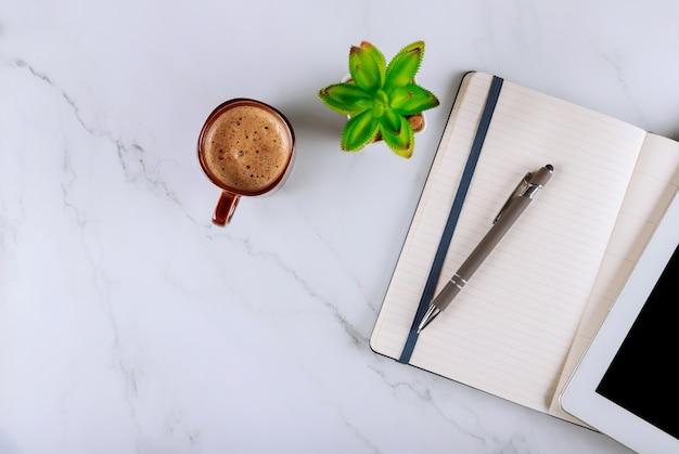 Tazza di caffè e tavoletta digitale con notebook, penna, tavolo scrivania