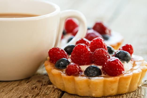Tazza di caffè e torte dolci con frutti di bosco