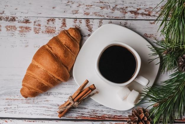 Tazza di caffè e un cornetto sul tavolo