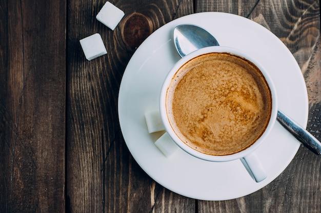 Tazza di caffè e zucchero freschi sul vecchio fondo rustico della tavola. concetto di mattina