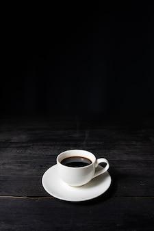 Tazza di caffè espresso sul tavolo nero vintage, vista frontale. caffè in tazza bianca su superficie scura con piacevole vecchia struttura di legno