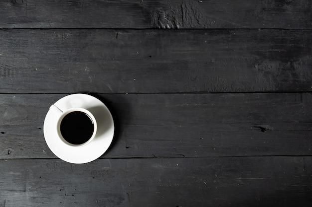Tazza di caffè espresso, vista dall'alto. immagine di stile piatto laici di caffè sulla superficie del legno nero in difficoltà
