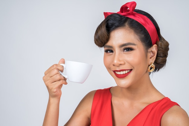 Tazza di caffè felice della tenuta della mano della donna di modo
