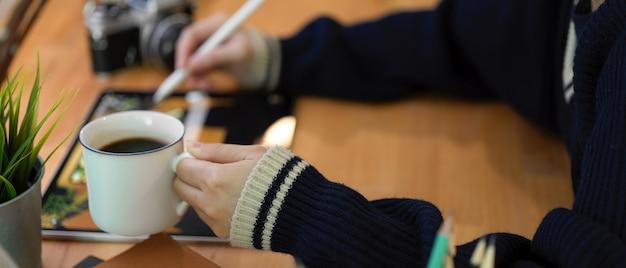 Tazza di caffè femminile della tenuta della mano sinistra mentre mano destra che lavora alla compressa digitale