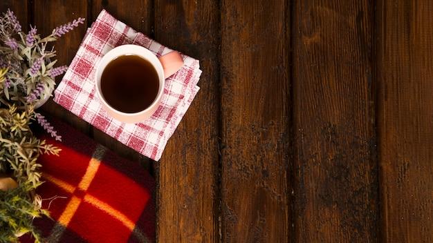 Tazza di caffè, fiori e coperta invernale su legno vecchio