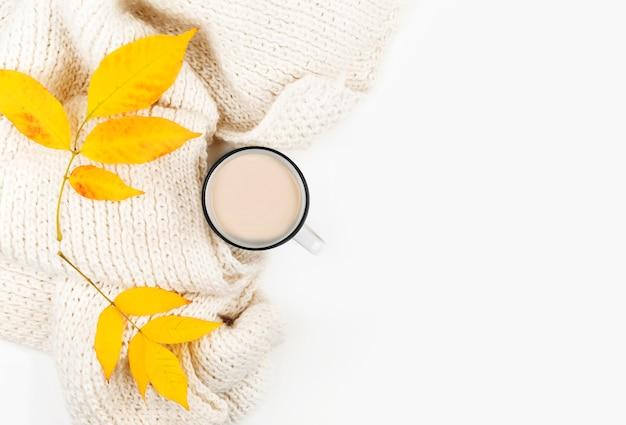Tazza di caffè, foglie di autunno, plaid su sfondo bianco.
