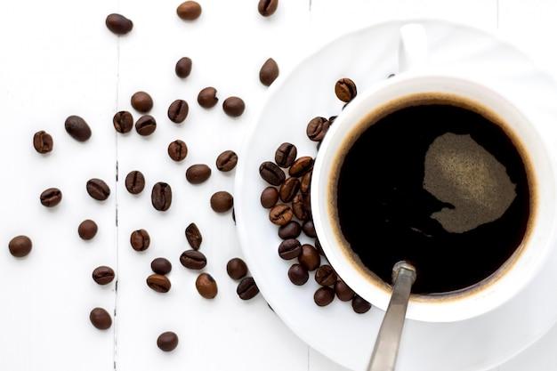 Tazza di caffè forte su un fondo di legno bianco con i grani