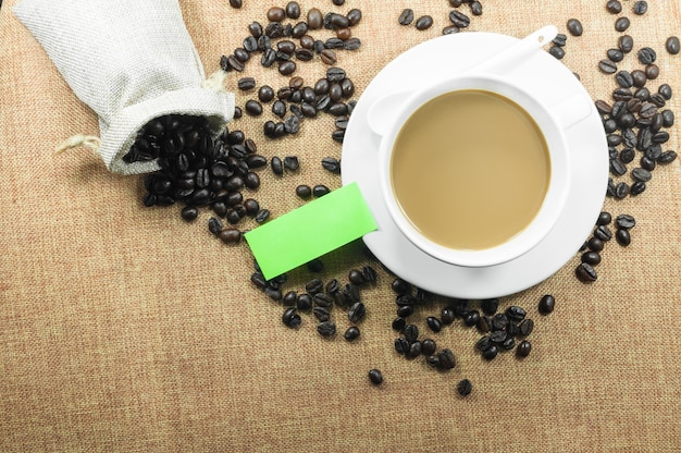 Tazza di caffè fresco con chicchi di caffè sulla tazza calda di tela da imballaggio