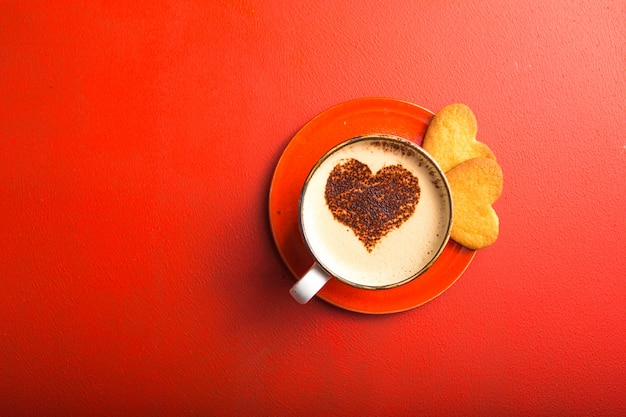 Tazza di caffè fresco con i biscotti del cuore sulla tavola rossa