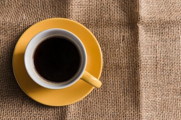 Tazza di caffè gialla con piastra su tela di sacco