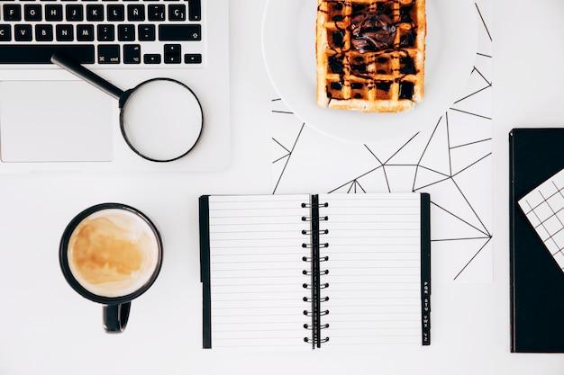 Tazza di caffè; il computer portatile; lenti d'ingrandimento; blocco note a spirale e cialde con cioccolato sul piatto contro scrivania bianca