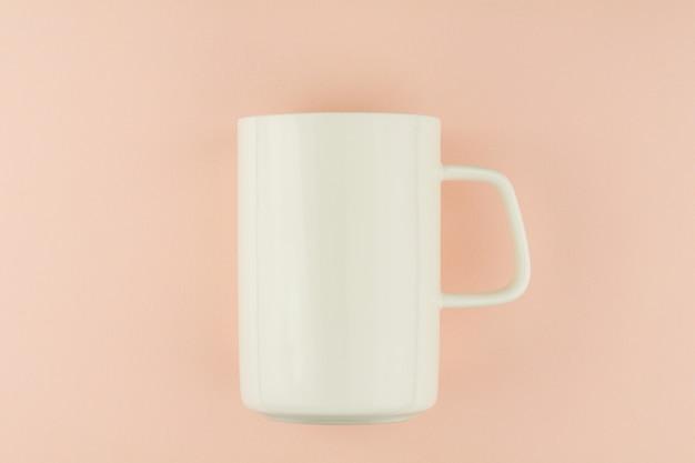 Tazza di caffè in ceramica bianca su sfondo rosa.
