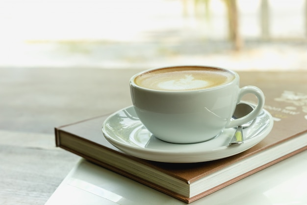 Tazza di caffè in cima al libro e al computer portatile sulla tavola di legno di mattina.