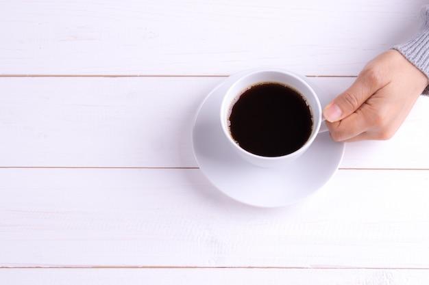 Tazza di caffè in mano femmina sul tavolo di legno bianco