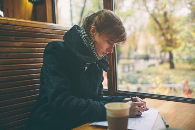 Tazza di caffè in primo piano con elegante giovane donna al tavolo di legno del negozio, uomini d'affari pausa di lavoro, luce chiarore del sole. autunno freddo, la femmina disegna o scrive nel diario