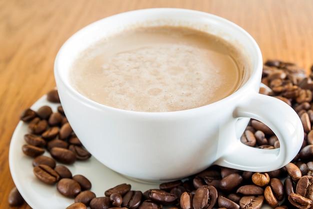 Tazza di caffè in una tazza bianca e chicchi di caffè sul fondo di legno della tavola, vista superiore.
