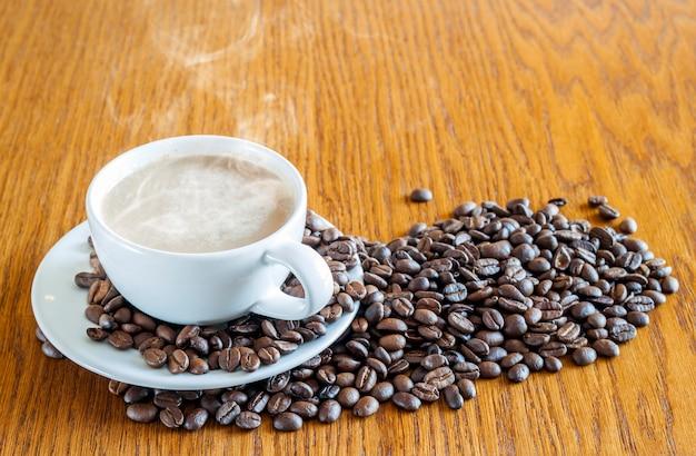 Tazza di caffè in una tazza bianca e chicchi di caffè sulle sedere di legno della tavola