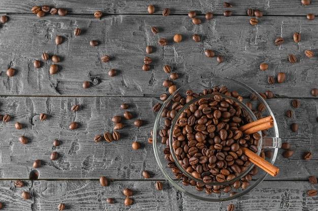 Tazza di caffè in vetro con chicchi di caffè su un tavolo nero con chicchi di caffè sparsi. la vista dall'alto. disteso. cereali per la preparazione della bevanda popolare.