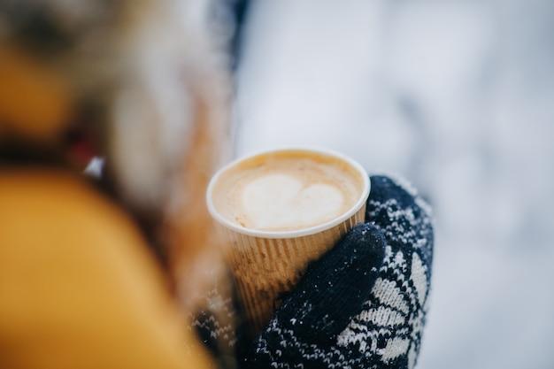 Tazza di caffè invernale. chicchi di caffè a forma di cuore in tazza