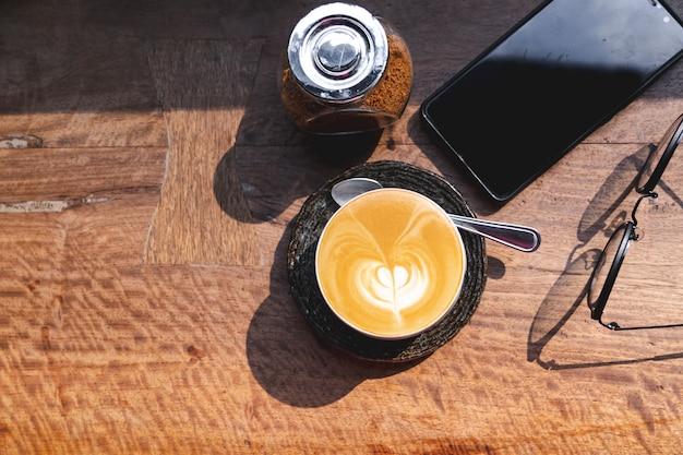 Tazza di caffè latte caldo con latte art, smartphone, occhiali e zucchero di canna