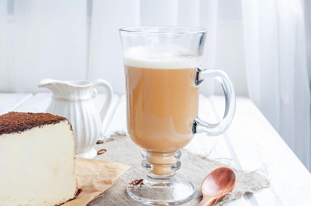Tazza di caffè latte con un pezzo di formaggio a pasta molle in caffè macinato