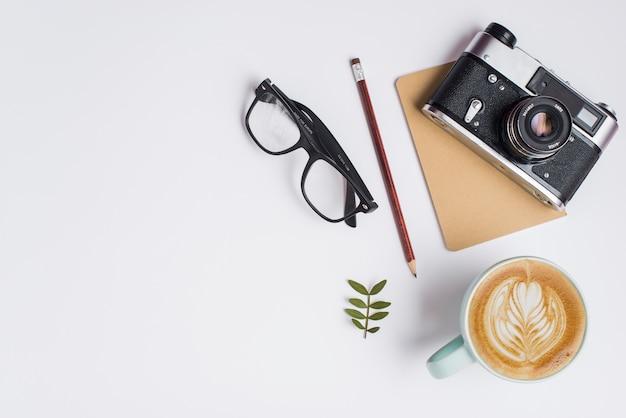 Tazza di caffè latte; matita; occhiali e macchina fotografica d'epoca su sfondo bianco