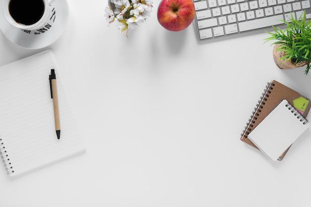 Tazza di caffè; mela e cartolerie sulla scrivania ufficio bianco