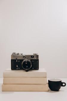 Tazza di caffè nera con la vecchia macchina fotografica d'annata e libri bianchi