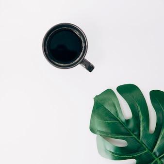 Tazza di caffè nera e foglia verde di monstera su fondo bianco