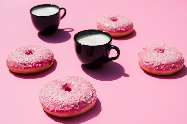 Tazza di caffè nero con ciambelle su sfondo rosa