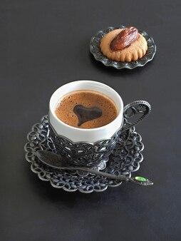 Tazza di caffè nero con forma di cuore e dolci arabi sul tavolo nero