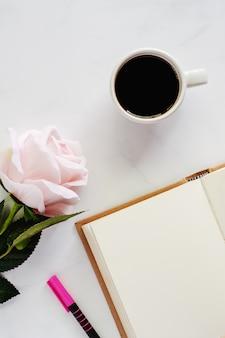 Tazza di caffè nero con il taccuino aperto, la penna e la rosa di rosa dolce su fondo di marmo bianco