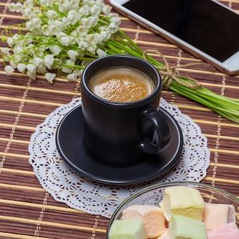 Tazza di caffè nero con latte su un piattino, marshmallows, un mazzo di mughetti