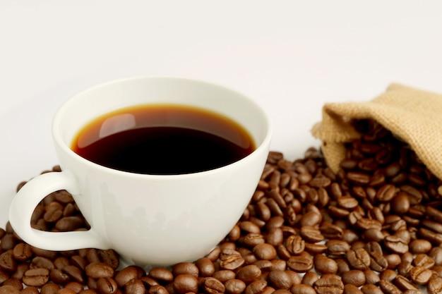 Tazza di caffè nero con un mucchio di chicchi di caffè tostati sparsi dal sacchetto di tela