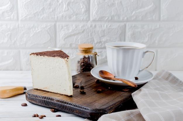 Tazza di caffè nero con un pezzo di formaggio morbido nel caffè macinato