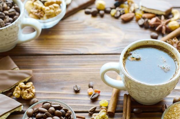 Tazza di caffè nero espresso su fondo di legno naturale con spuntini sani - noci e uvetta. copia spazio nel mezzo.
