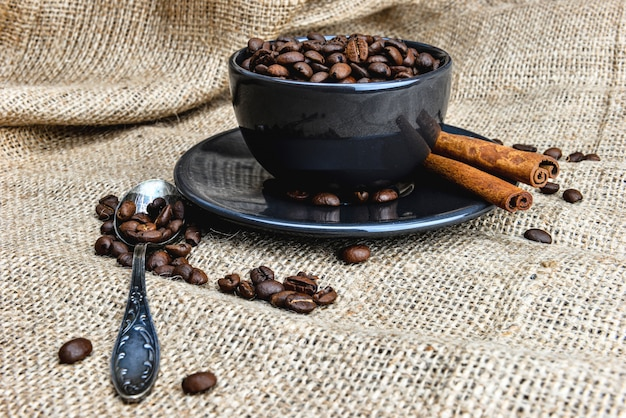 Tazza di caffè nero pieno di chicchi di caffè biologici e bastoncini di cannella sul panno di lino