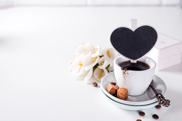 Tazza di caffè nero su un piattino con zucchero di canna su uno sfondo bianco