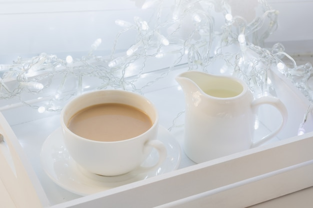 Tazza di caffè nero sul davanzale invernale con ghirlanda. vacanze di natale. periodo natalizio.
