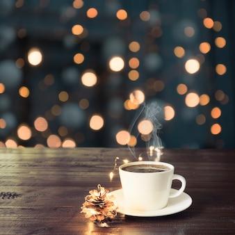 Tazza di caffè nero sulla tavola di legno in caffè. luci di natale