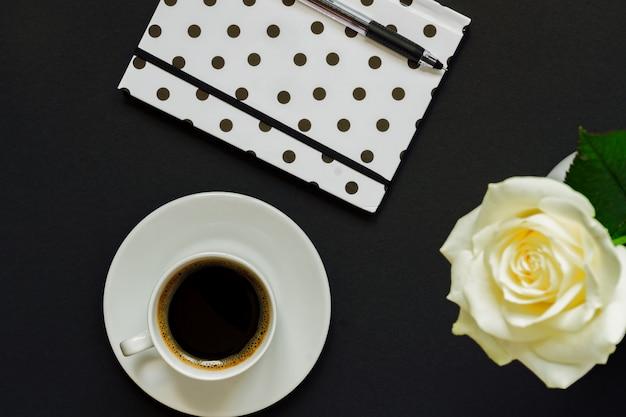 Tazza di caffè nero, taccuino e rosa bianca su