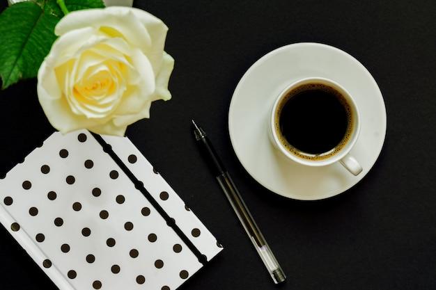 Tazza di caffè nero, taccuino e rosa bianca sul nero