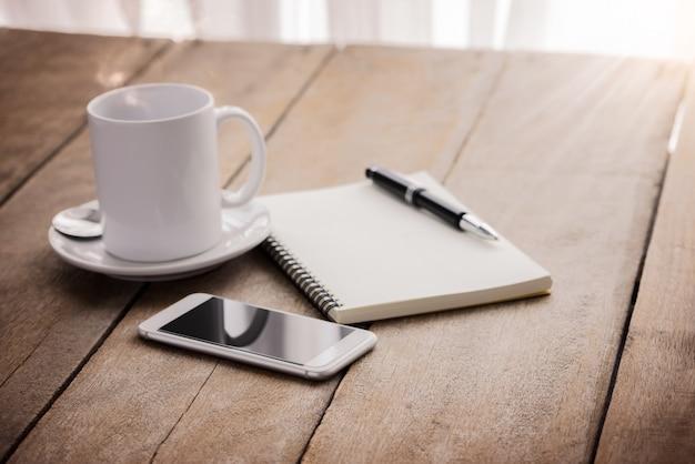 Tazza di caffè, notebook, penna e smart phone