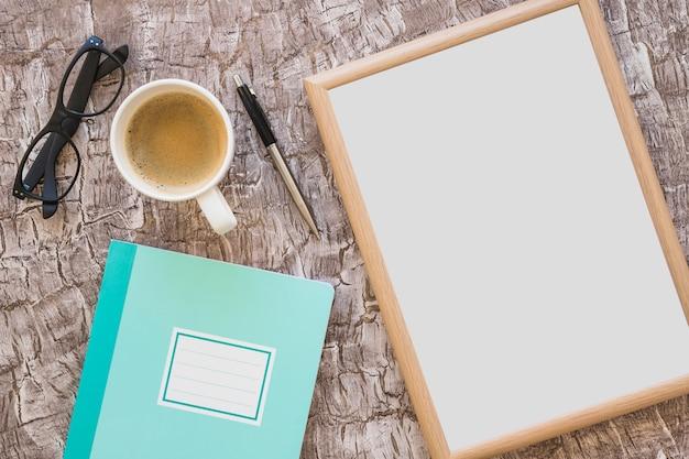 Tazza di caffè; occhiali; penna; cornice e notebook su sfondo con texture