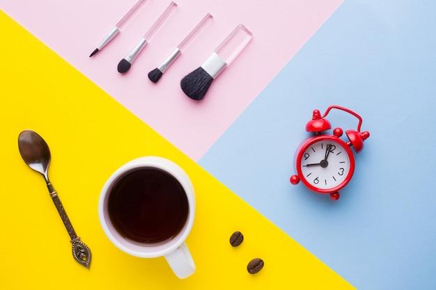 Tazza di caffè, orologio e pennelli per il trucco. concetto di mattina.
