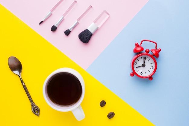 Tazza di caffè, orologio e pennelli per il trucco