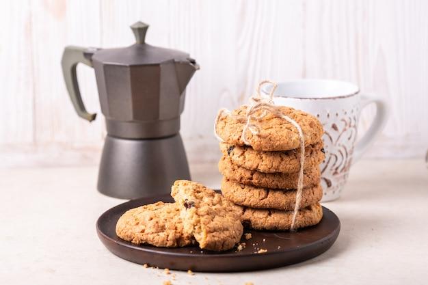 Tazza di caffè, pila di biscotti di farina d'avena, caffettiera, prodotti da forno fatti in casa