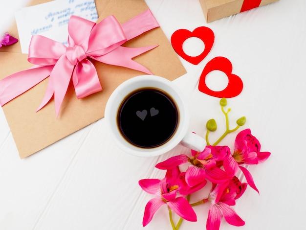 Tazza di caffè, regali rosa vicino, lettere e due cuori nella tazza.