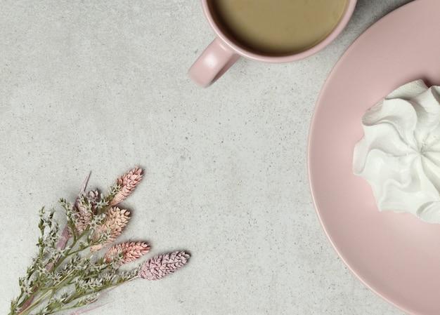 Tazza di caffè rosa, marshmallow, bouquet di fiori bianchi sulla trama di granito