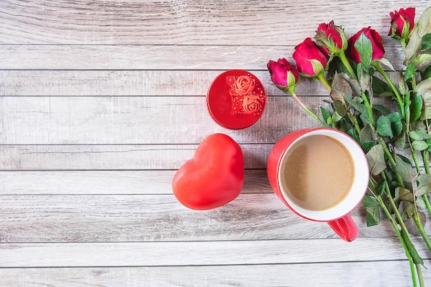 Tazza di caffè rossa con cuore e rosa concetto di giorno di san valentino